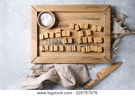 Salted Caramel Fudge Candy Served On Wooden Tray With Fleur De Sel In Wood Bowl And Knife Over Grey