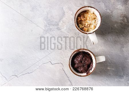 Chocolate And Vanilla Caramel Mug Cakes From Microwave Over Grey Texture Background. Top View, Copy