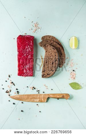 Piece Of Beetroot Marinated Salted Salmon With Sliced Rye Bread, Pink Salt, Pepper, Lime And Wooden