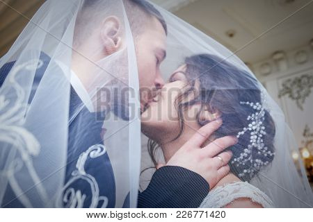 Under The Veil, The Bridegroom Kisses The Bride With Closed Eyes. The Faces Of Young People Are Slig