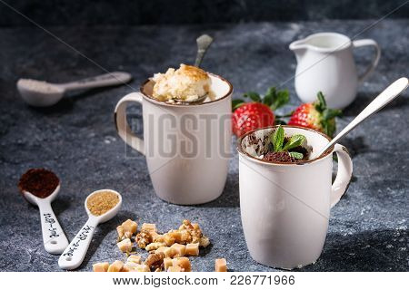 Chocolate And Vanilla Caramel Mug Cakes From Microwave With Fresh Strawberries And Ingredients Above