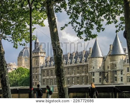 Paris, France - May 29, 2006: People Go Along Seine Riverside Near Palace Conciergerie On May 29, 20