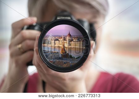 Budapest, Hungary - Young Happy Blonde Tourist Woman In Grey Coat And Sunglasses Taking Photos Of Bu