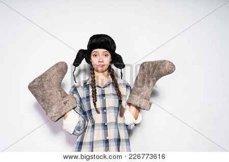 Funny Young Russian Girl In A Hat With Ear-flaps Holds Warm Felt Boots