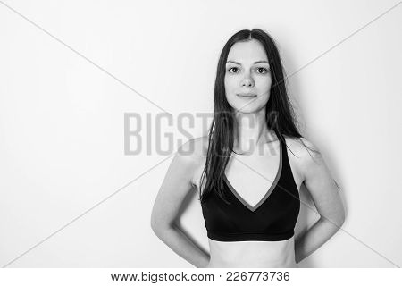 Brunette Woman With Long Hair In A Tube Top Stands At The Wall And Looks At The Camera. Hands Behind