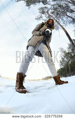A Young And Joyful Caucasian Girl In A Brown Coat Holds A Snowball In Front Of A Horizon Line Betwee