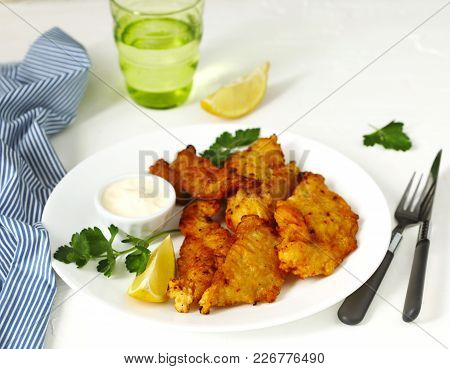 Golden Batter Deep Fried Fish Fillets, Served On White Plate With Sauce And Lemon