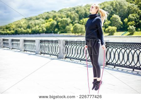 Woman Feet Jumping, Using Skipping Rope In Park. Beautiful Sports Girl Doing Cardio Exercises.