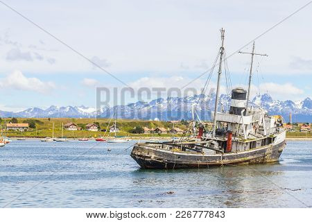 Old Boat In Beagle Channel With Mountains And Houses In Ushuaia