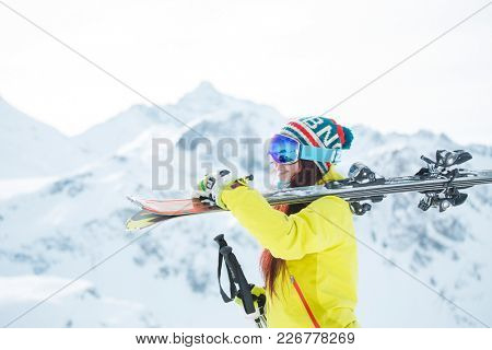Photo of smiling woman in mask with skis on her shoulder