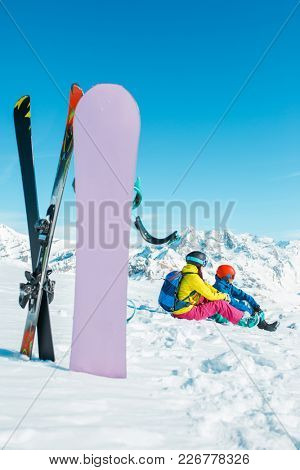 Picture of snowboard, skis on background of sitting sports woman and man on snowy hill