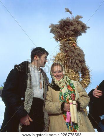 Couple Near Straw Scarecrow