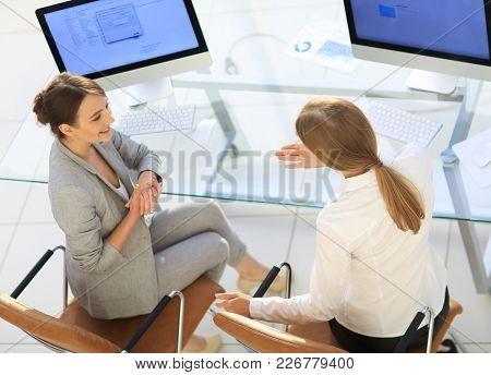 view from the top rear.business woman talking with a colleague sitting near the desktop
