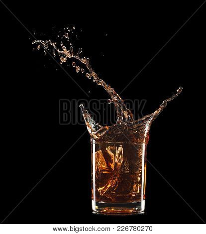 Glass Of Whiskey With Splash Isolated On Black Background.