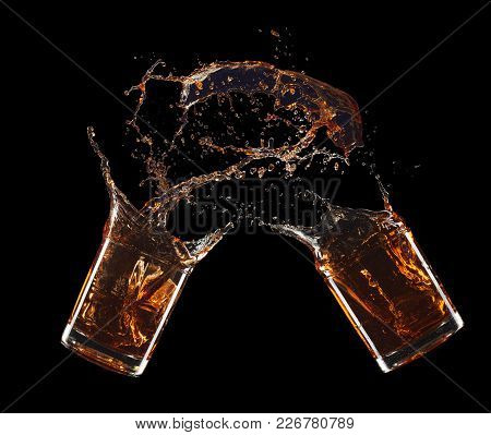 Two Glass Of Whiskey Splashing Isolated On Black Background.