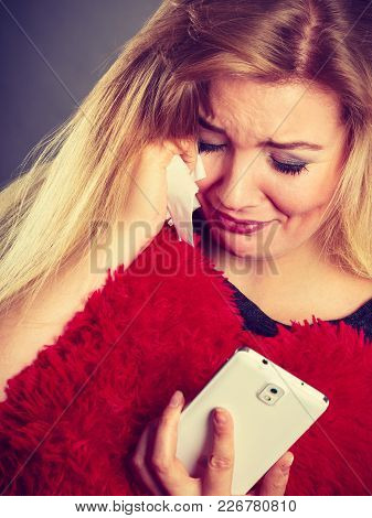 Betrayal, Bad Relationship, Hurt Love Concept. Sad Heartbroken Woman Crying And Looking At Her Phone