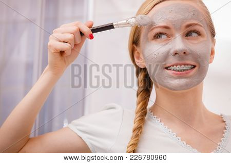 Facial Dry Skin And Body Care, Complexion Treatment At Home Concept. Happy Young Woman Applying Grey