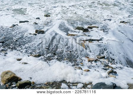 Sea Wave Rolls Down From The Stone Shore, Leaving The Foam On The Beach
