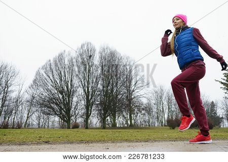 Woman Wearing Sportswear Exercising Outside During Autumn