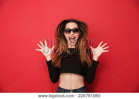 Photo of excited young woman standing isolated over red background. Looking camera.