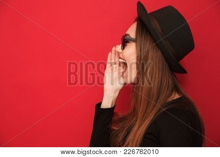 Side view picture of young screaming woman standing isolated over red background. Looking aside.