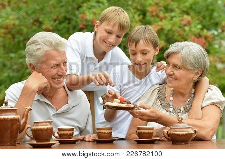 Grandparents With  Grandsons Eating At Outdoor Table In Summer Time