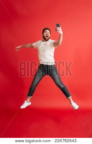 Photo of excited bearded man jumping isolated over red background wall using mobile phone make selfie.