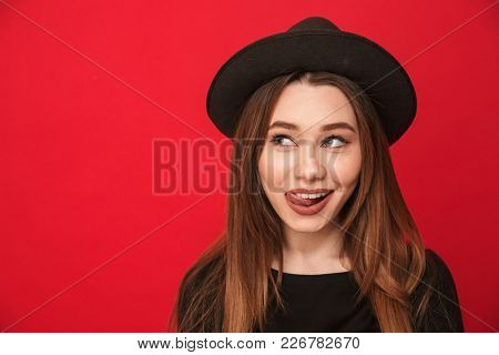 Photo of happy young woman standing isolated over red background. Looking aside licking her lip.