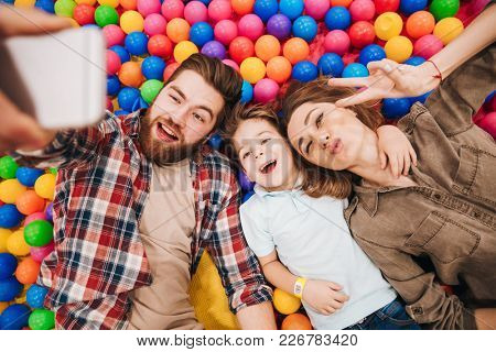 Photo of happy little child have fun with his parents in entertainment game center. Looking aside make selfie by phone showing peace gesture.