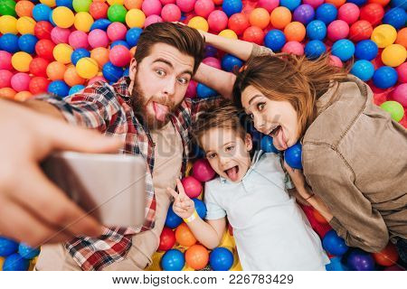 Image of happy little child have fun with his parents in entertainment game center make selfie by phone.