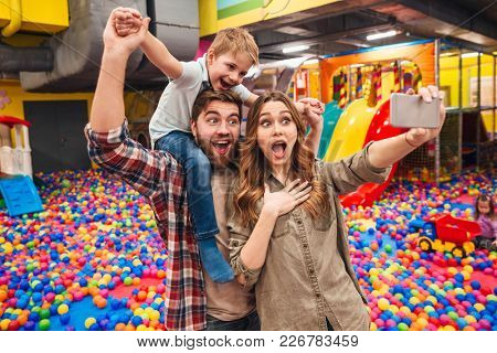 Picture of happy little child have fun with his parents in entertainment game center. Looking aside make selfie by phone.