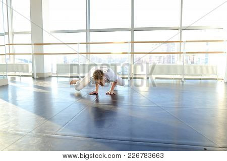 Athletic Guy Sitting On Twine, Tilting Trunk And Doing Stretching. Male Person Trying To Be In Good