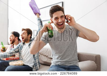 Image of young bachelors rcelebrating victory of favorite team while watching football game at home with beer and snack