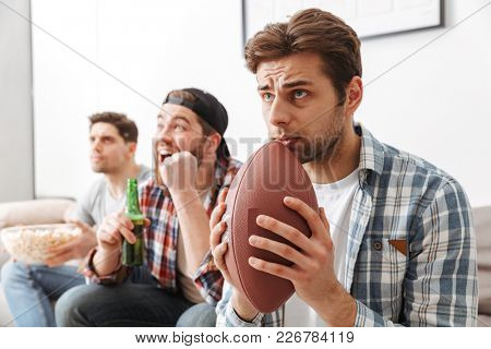 Image of involved male sport lovers worrying while rooting for football team at home