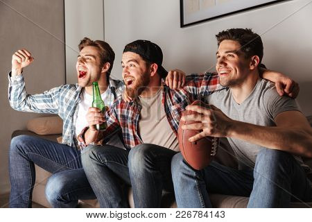 Photo of satisfied bachelors shouting happily while partying at home and watching football game with beer
