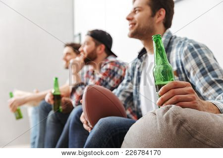 Photo in profile of pleased men 30s resting at home and watching football game on tv with drinking beer