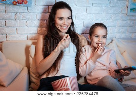 Mother And Little Daughter Watching Movies On Television At Night At Home.