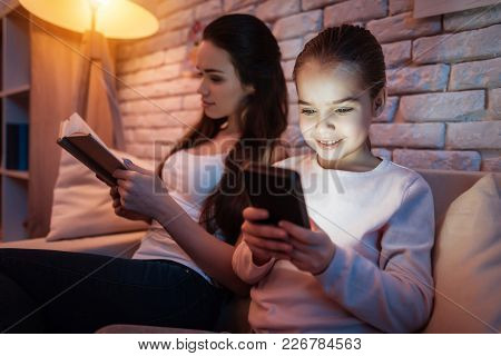 Mother Is Reading Book And Little Daughter Is Playing On Phone At Night At Home.