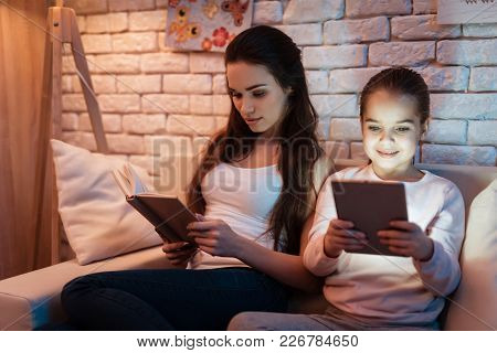 Mother Is Reading Book And Little Daughter Is Playing On Tablet At Night At Home.