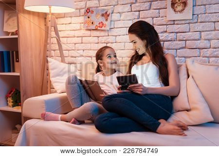 Mother And Little Daughter Reading Book And Playing On Tablet On Laptop At Night At Home.