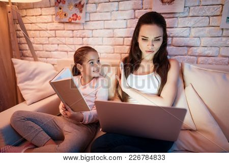 Little Daughter Wants Nother To Read Book But Mother Is Busy On Laptop At Night At Home.