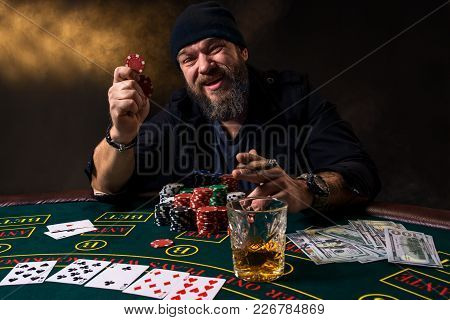 Bearded Man With Cigar And Glass Sitting At Poker Table In A Casino. Gambling, Playing Cards And Rou