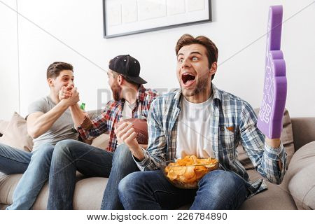 Photo of satisfied bachelors shouting happily while partying at home and watching football game with beer and chips