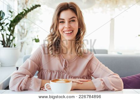 Image of attractive woman with auburn hair sitting alone in city cafe with cup of coffee beverage and looking on camera