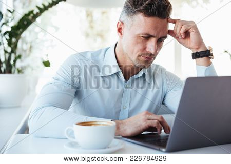 Portrait of a pensive mature man using laptop computer while sitting at the cafe table indoors