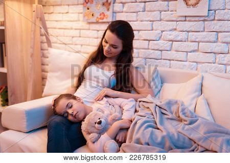 Daughter Is Sleeping On Mother's Lap Late At Night At Home.