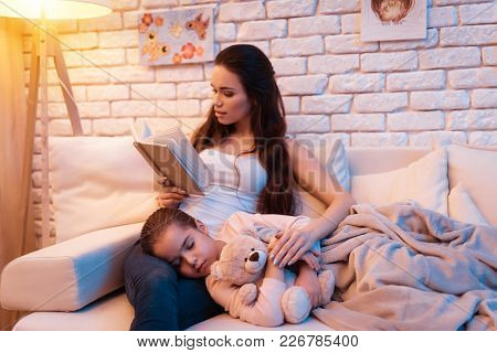 Daughter Is Sleeping On Mother's Lap While She Is Reading Book Late At Night At Home.