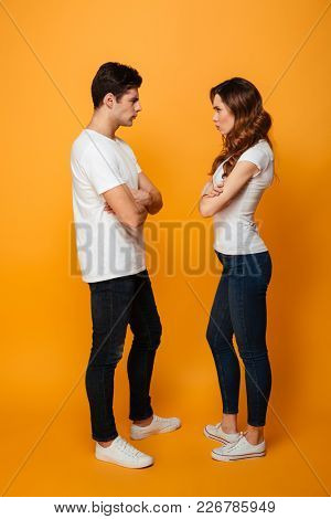Full length image of Serious displeased young lovely couple standing with crossed arms and looking to each other over yellow background