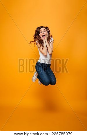 Full length image of Surprised brunette woman in t-shirt jumping and looking at the camera with open mouth while holding her cheeks over yellow background