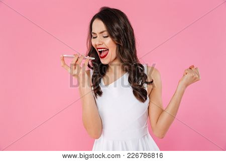 Photo of excited asian woman with red lips screaming on mobile phone and clenching fist isolated over pink background